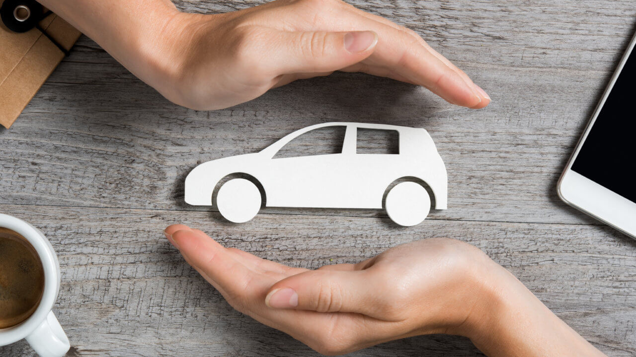 Hands protecting icon of car over wooden table